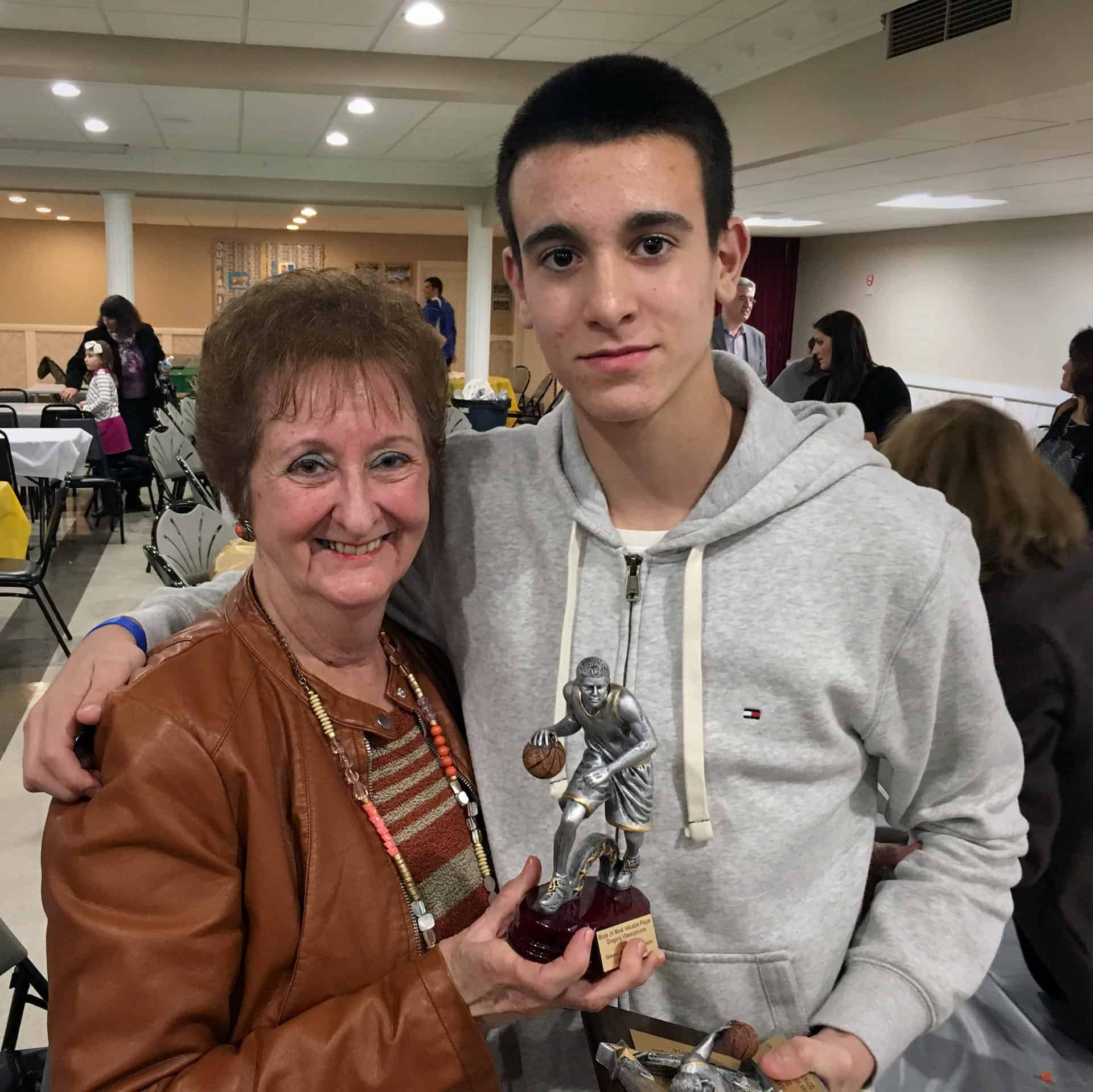 Greg Vlassopoulos with his grandmother at the GOYA Awards Ceremony holding the MVP trophy